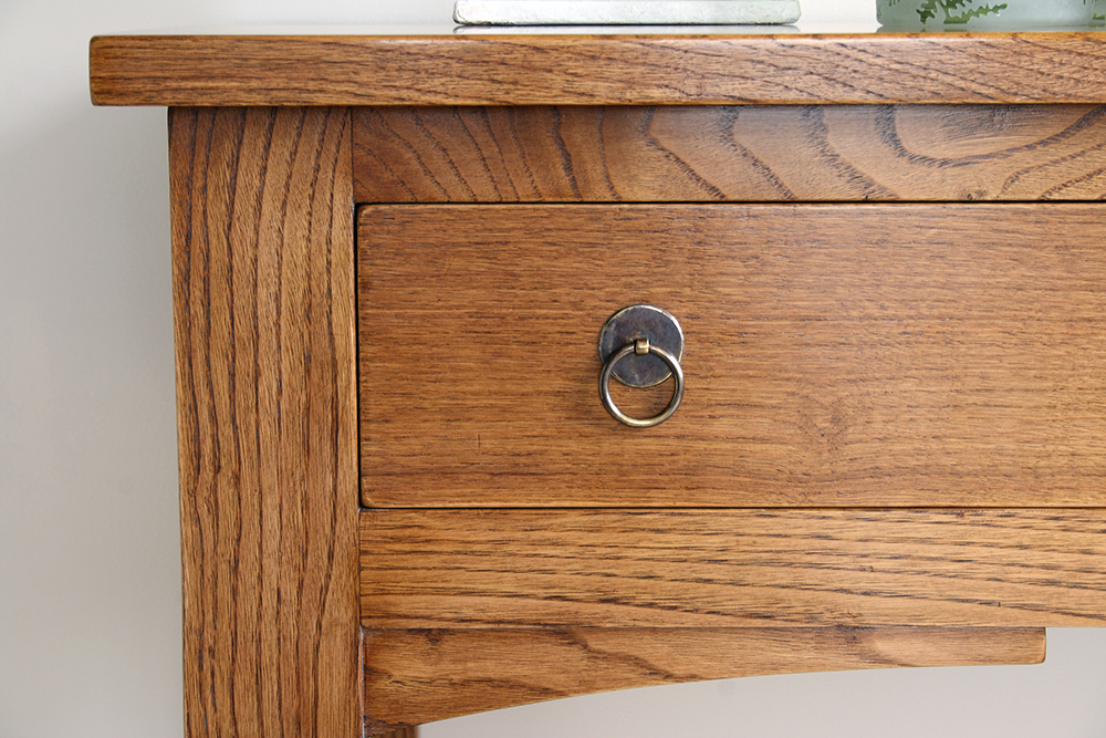 A close-up of the side-table with its arch detailing and simple circular drawer pulls