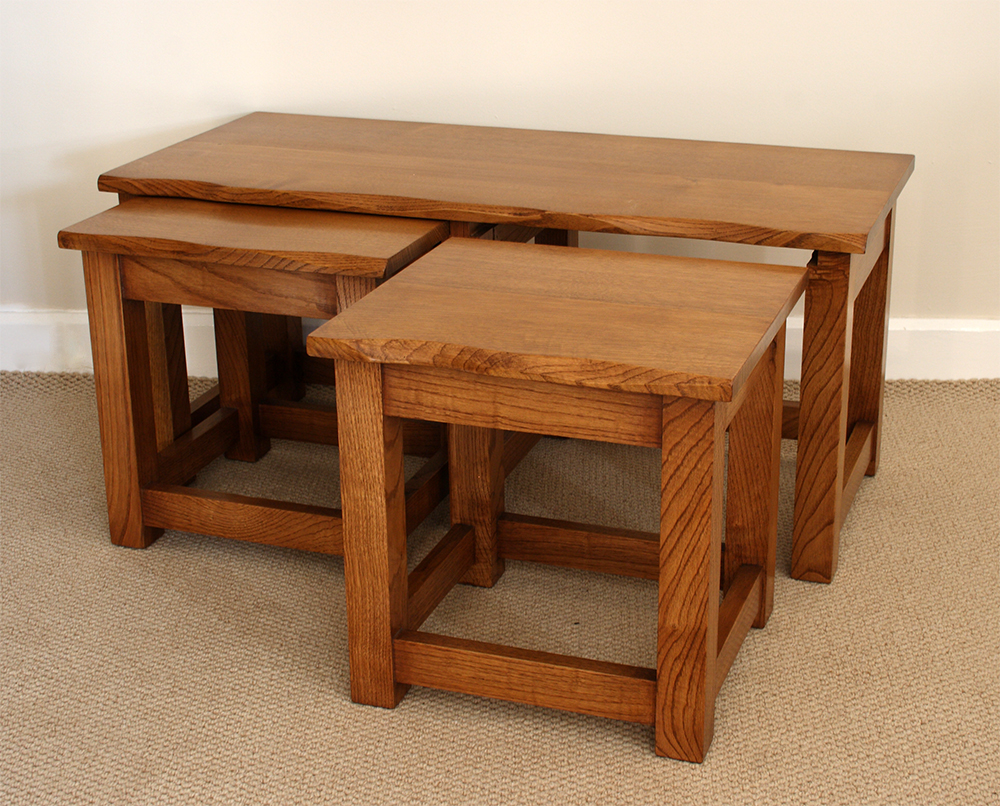 Nest of three chestnut occasional tables with wavy edge