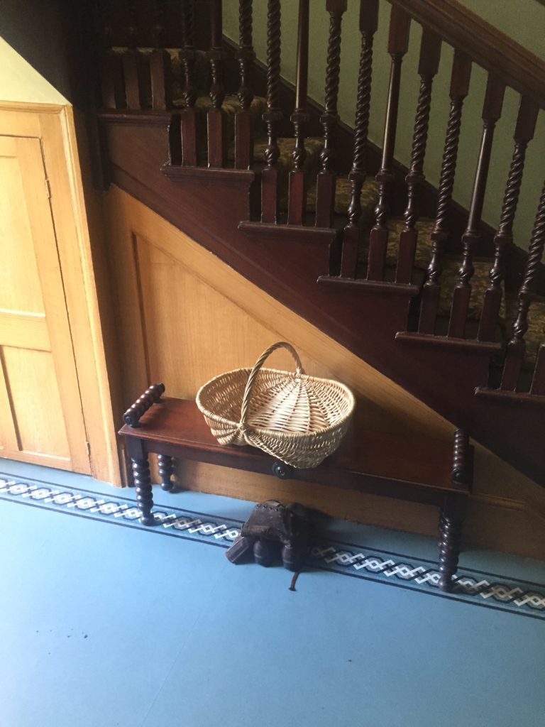 A trug and a pair of boots sit in the hall