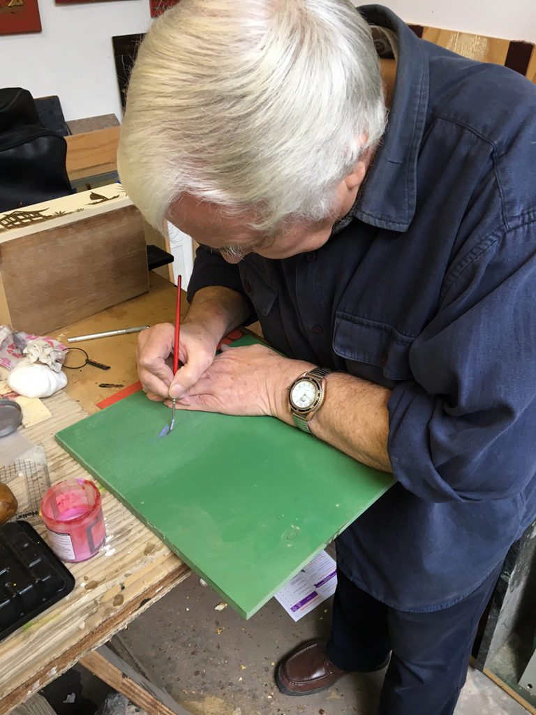 Dave drawing a design onto a piece of wood ready for gilding
